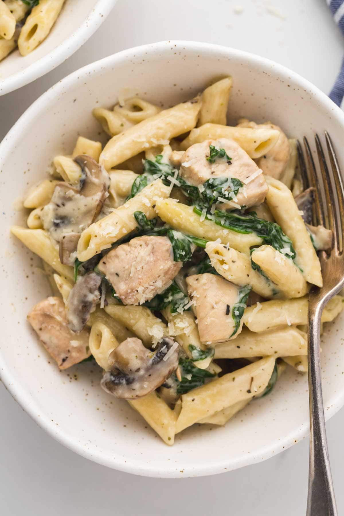 Close up of chicken florentine pasta in a white bowl with a fork on the side