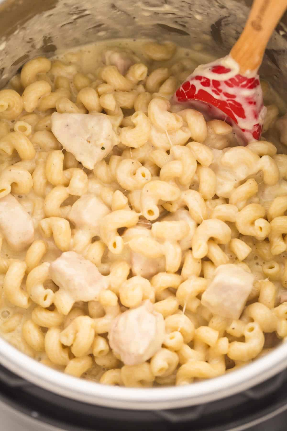 A close up shot of Instant Pot mac and cheese in the Instant Pot with a red spatula
