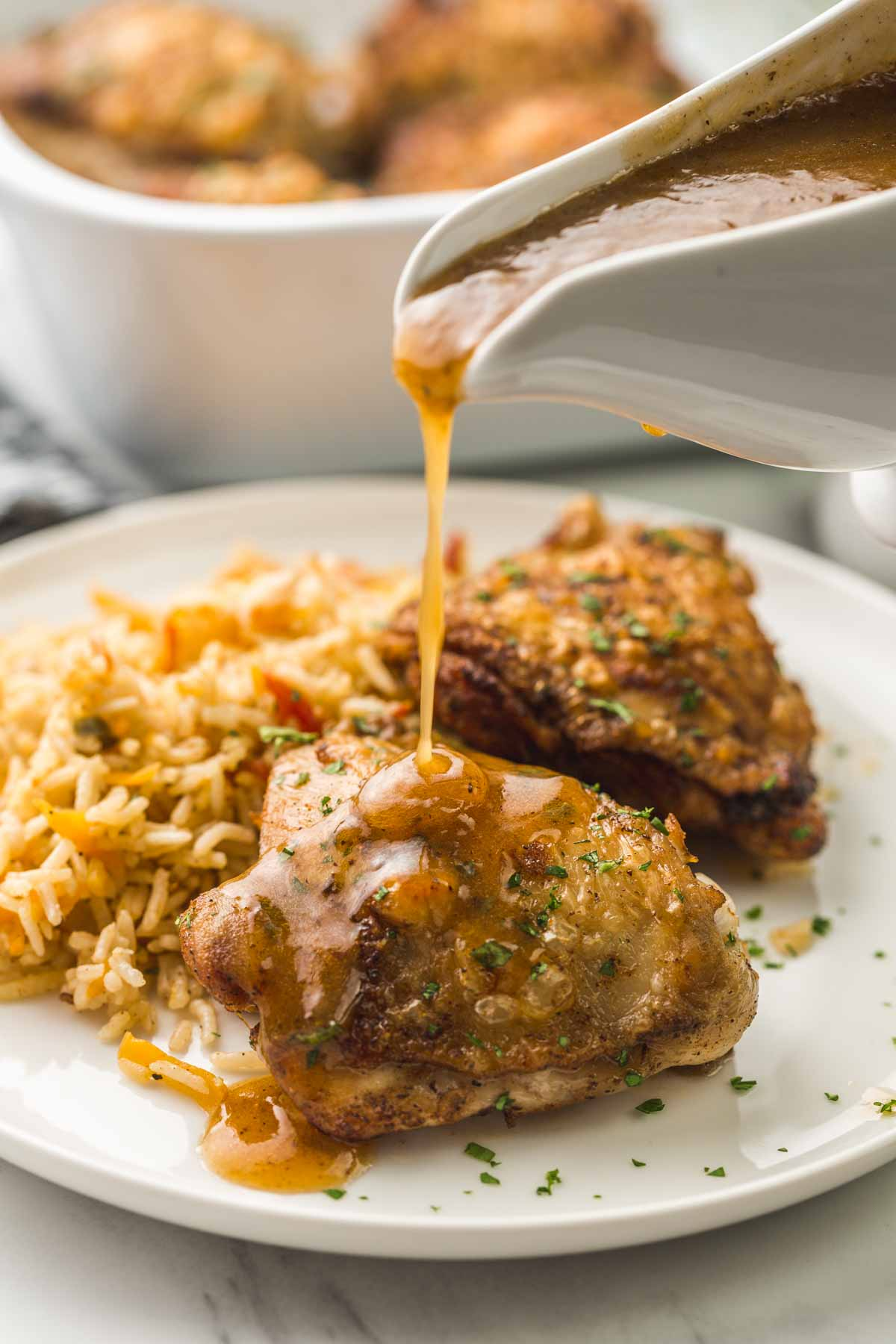 Pouring gravy over the chicken thighs
