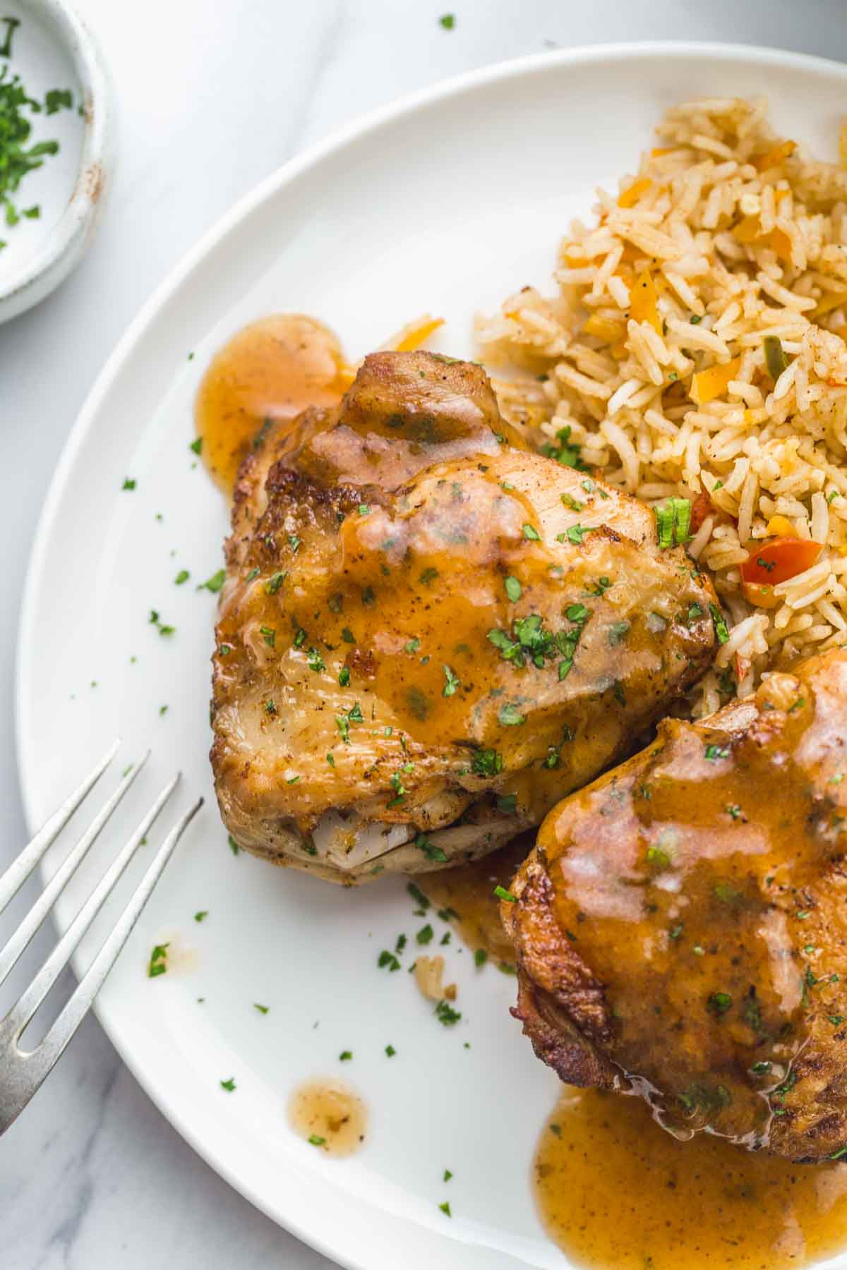 Chicken thighs served with rice, and gravy.