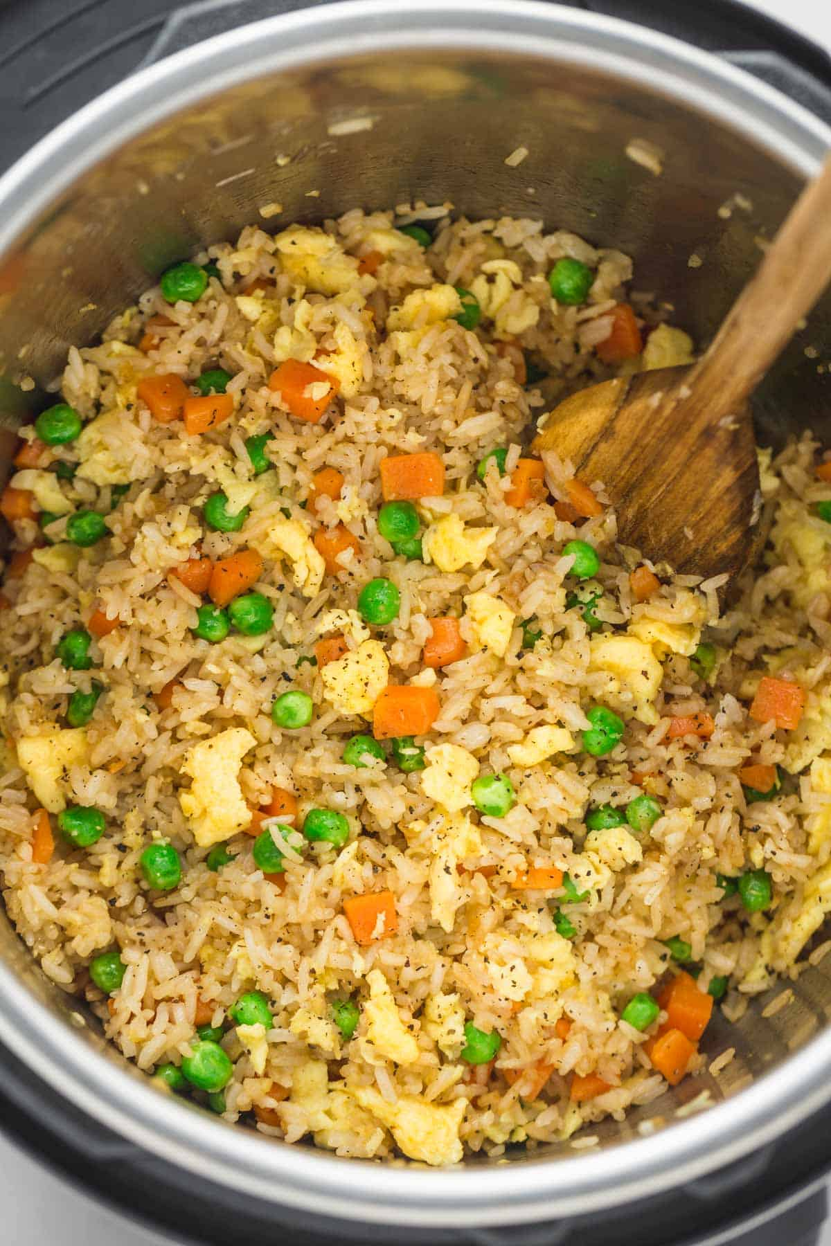 Fried rice in the instant pot with a wooden spoon