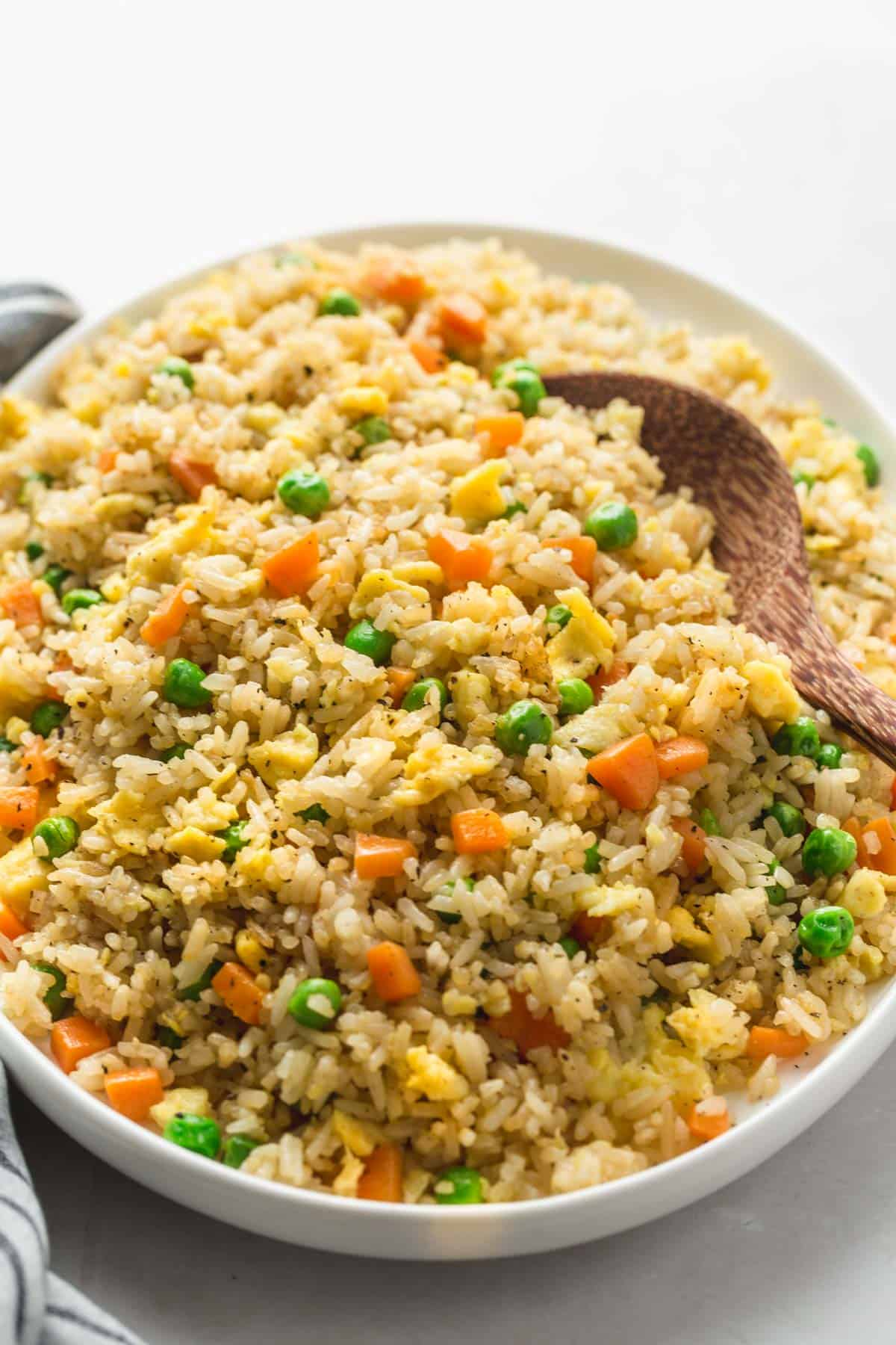 A large plate with fried rice served in it, and a wooden serving spoon