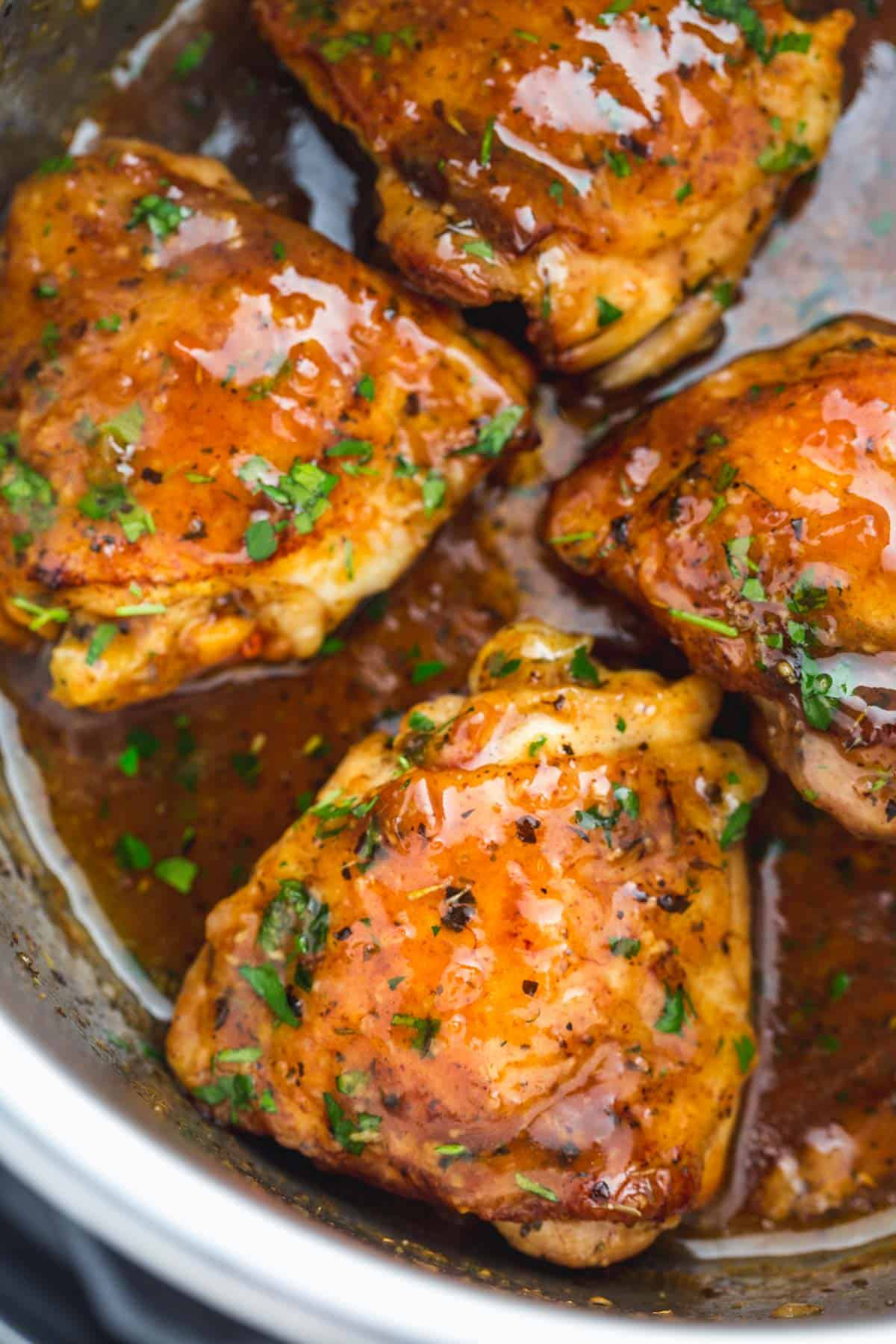 A close up of 4 cooked chicken thighs with brown sugar sauce and chopped parsley in the Instant Pot