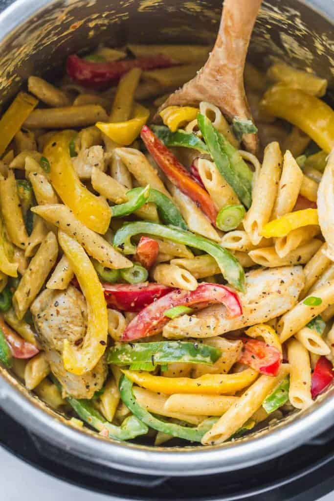 Cooked Rasta Pasta in an instant pot with a wooden serving spoon