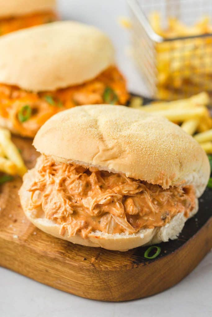 Creamy salsa shredded chicken sliders with French fries on a wooden board