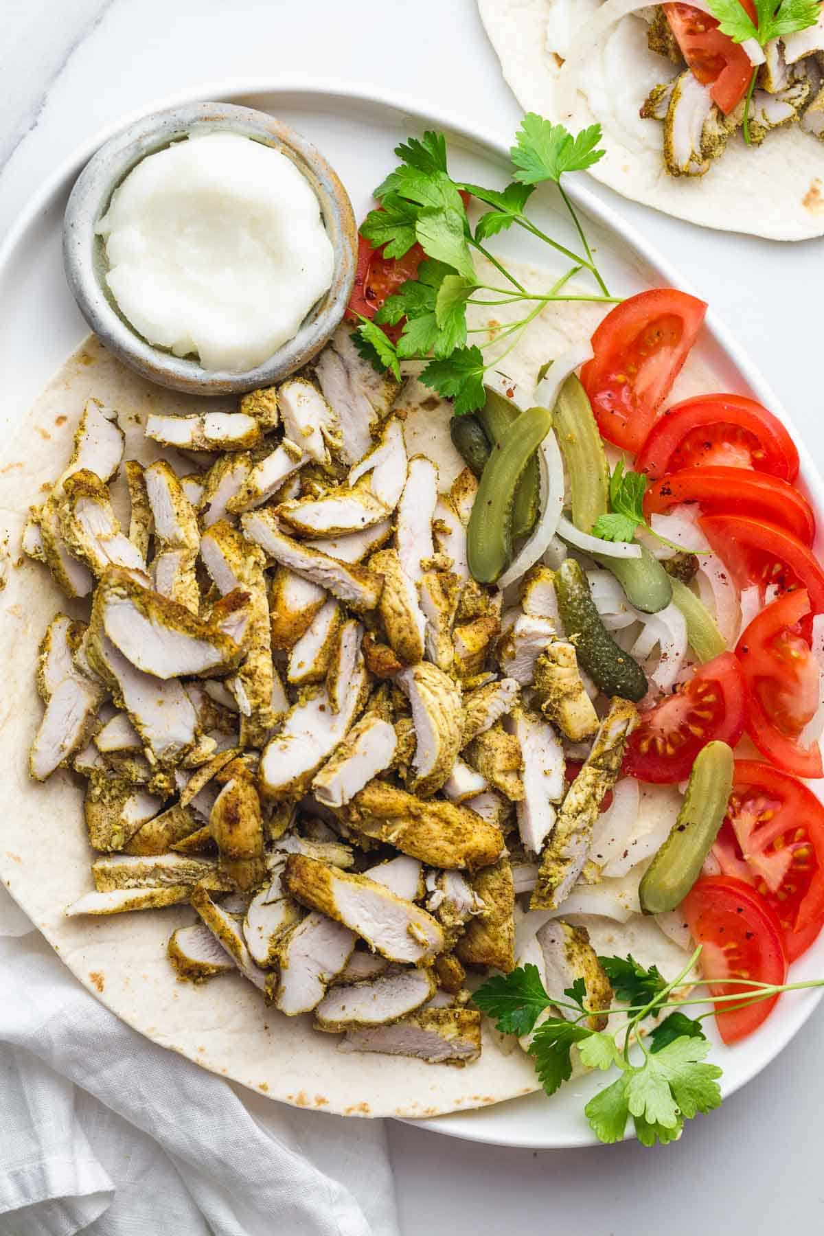 A chicken shawarma platter with sliced tomato, sliced onion, and pickles