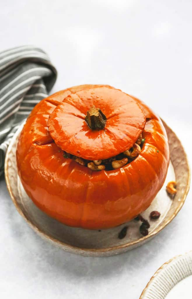 A whole pumpkin that is stuffed and cooked, on a serving plate
