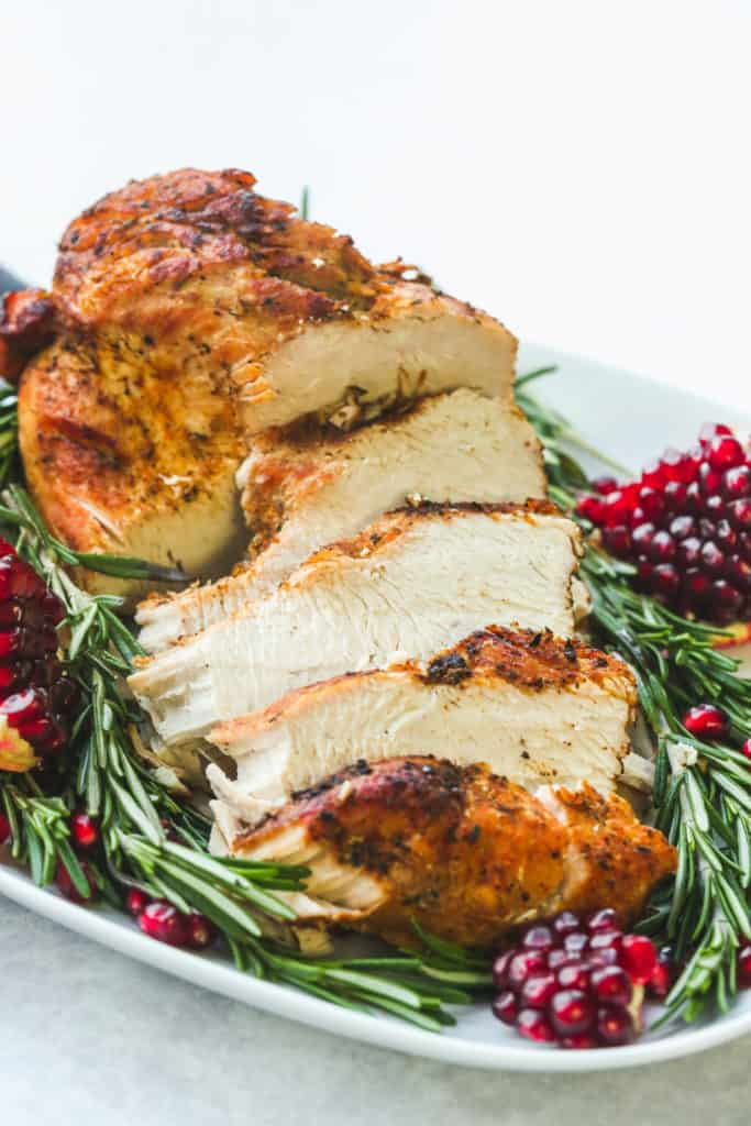 Slice instant pot turkey breast in a platter with rosemary and pomegranate seeds