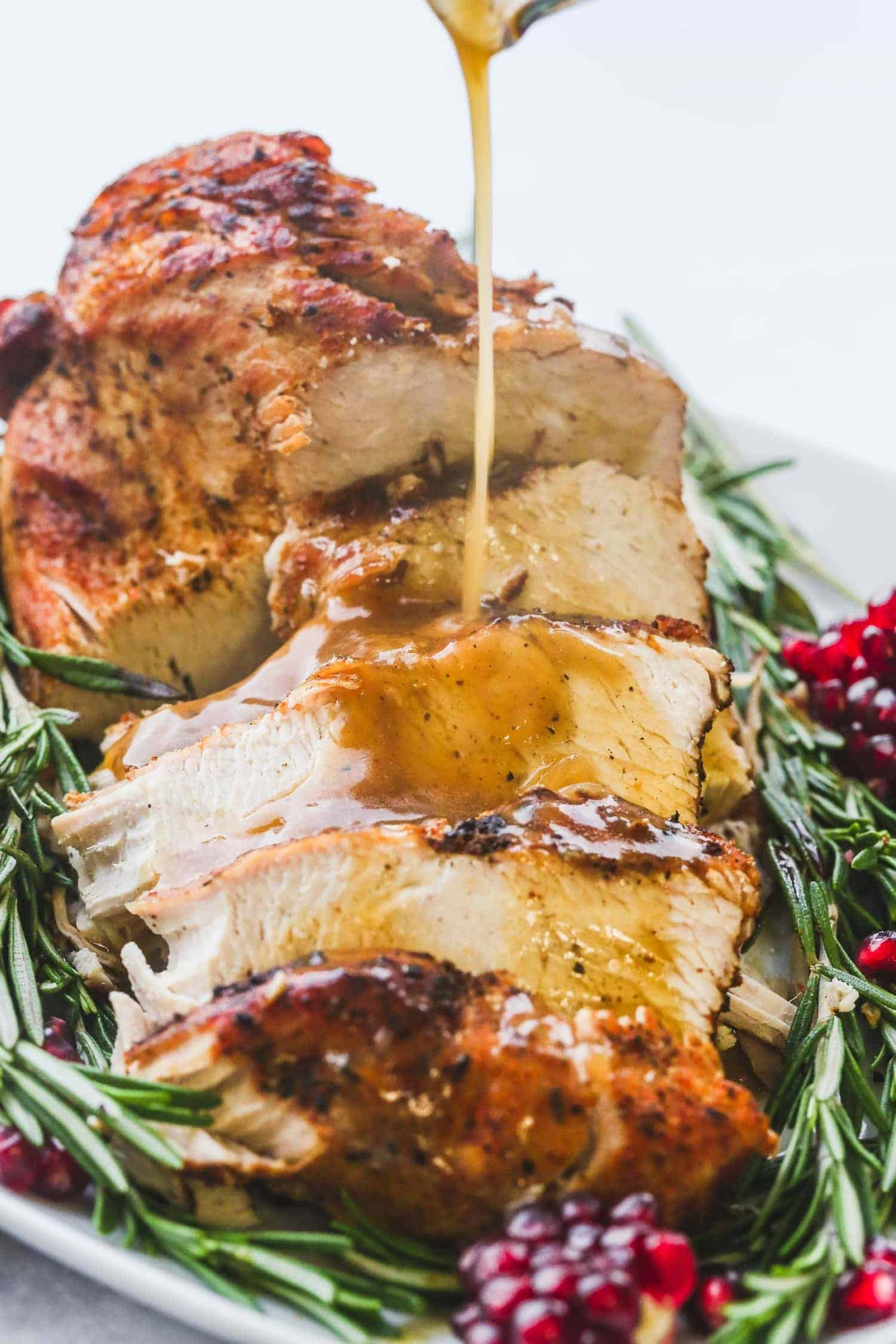 Pouring homemade turkey gravy over  sliced instant pot turkey breast