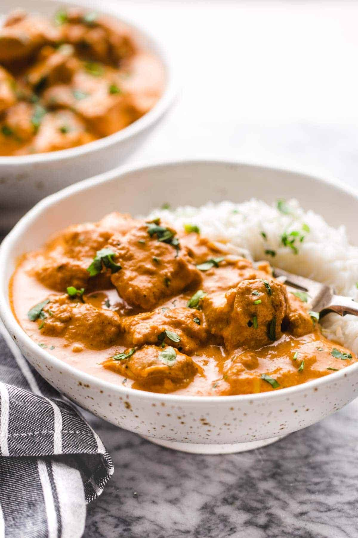 Two bowls of butter chicken served with rice and topped with chopped cilantro.