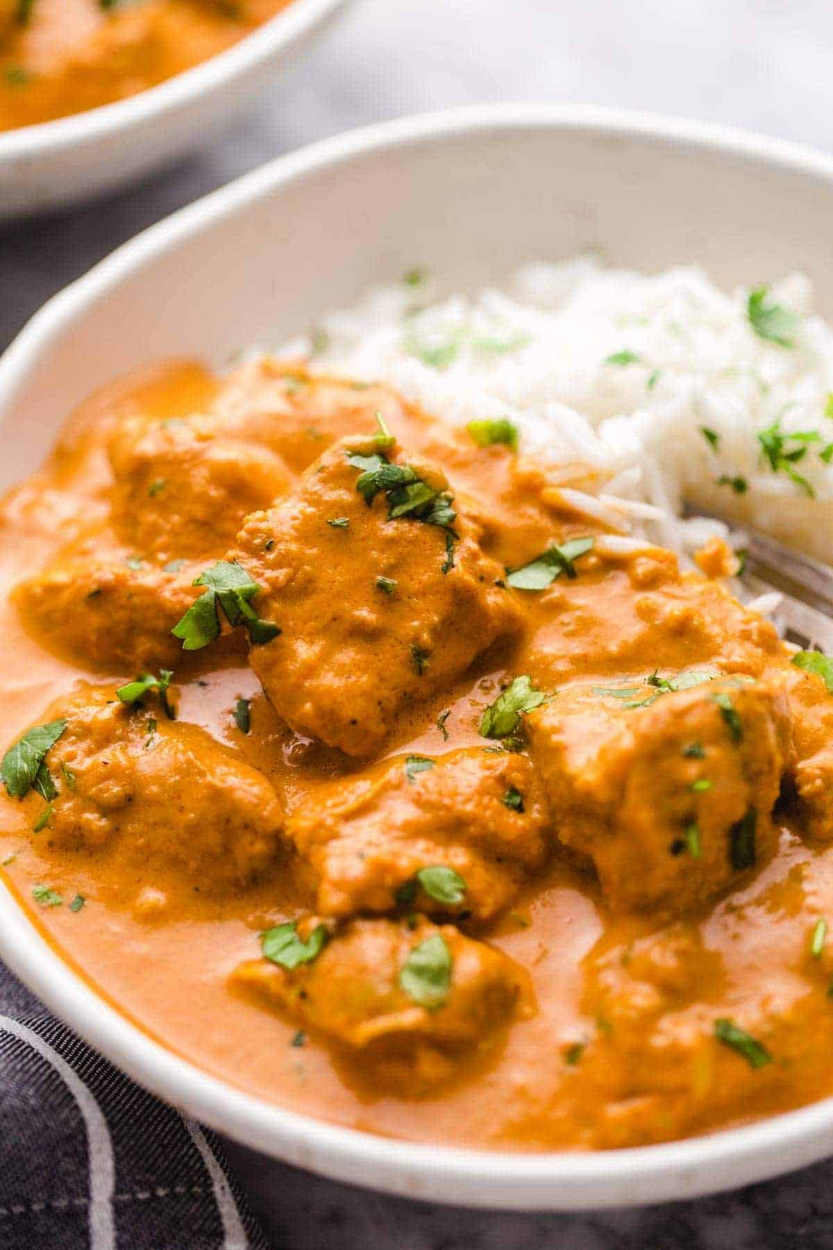 Butter chicken served with rice in a white bowl.