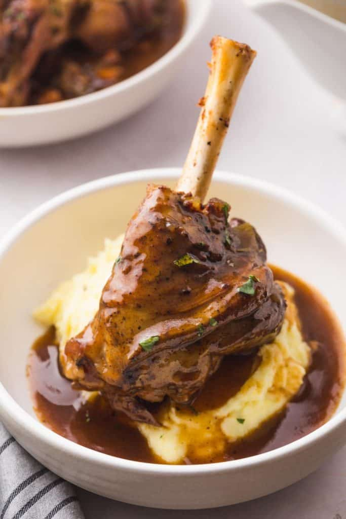 lamb shank served over mashed potatoes and plenty of gravy
