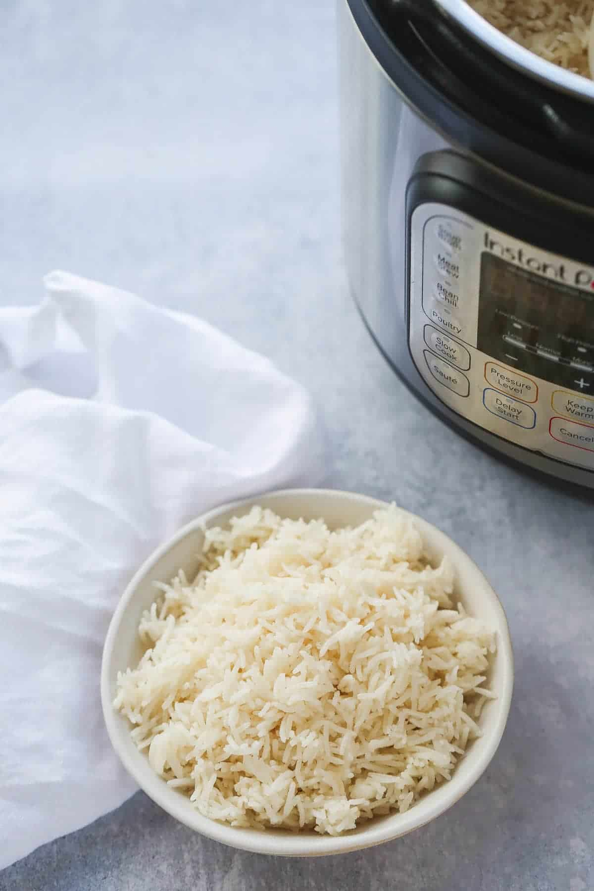 A white bowl with rice and an instant pot in the background