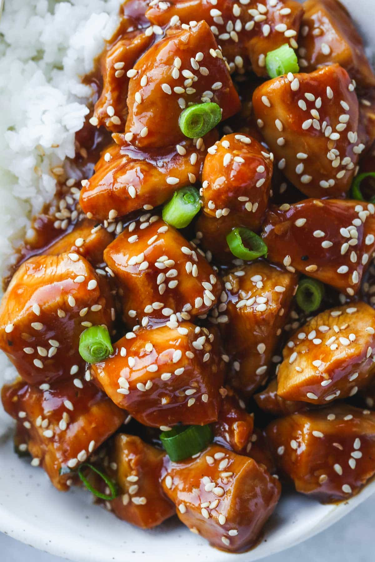 Close up shot of honey sesame chicken over rice, garnished with sesame seeds and green onion