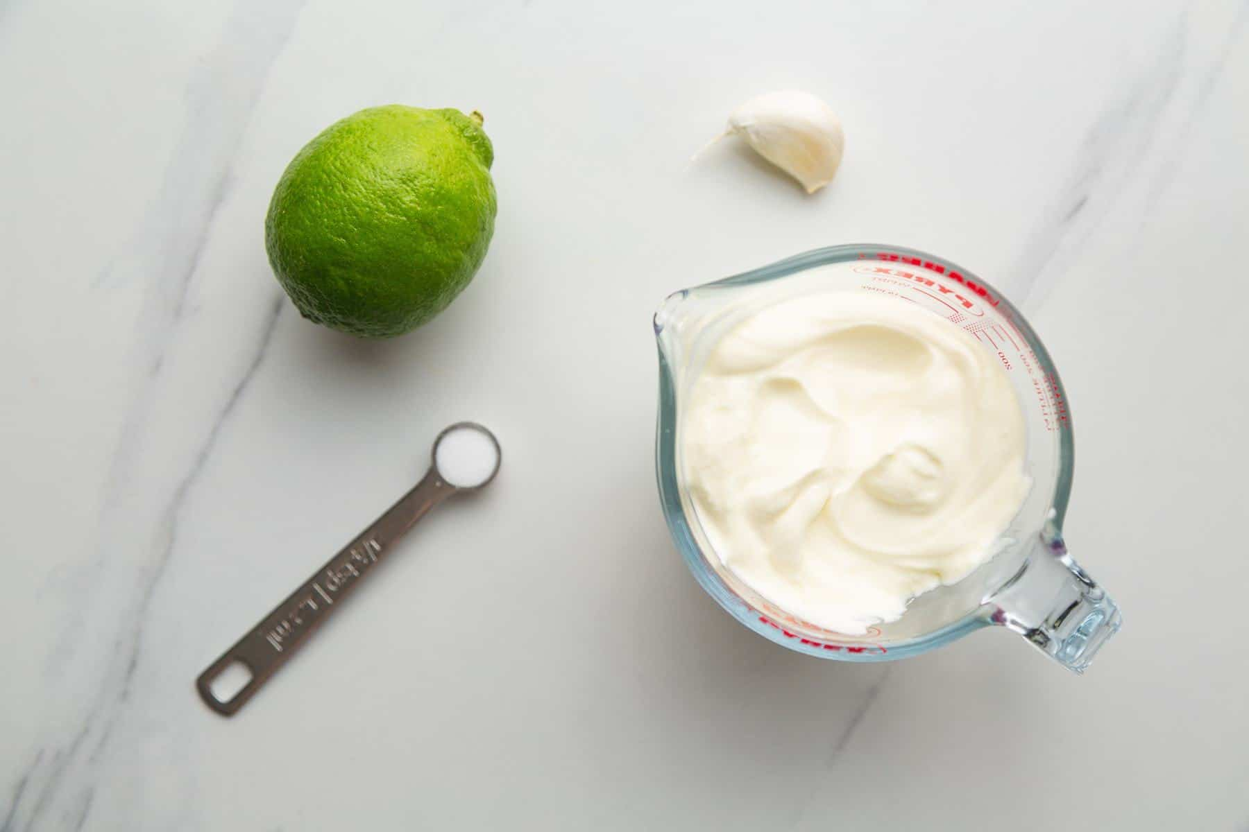 Lime Crema ingredients, sour cream, lime, garlic, and salt.