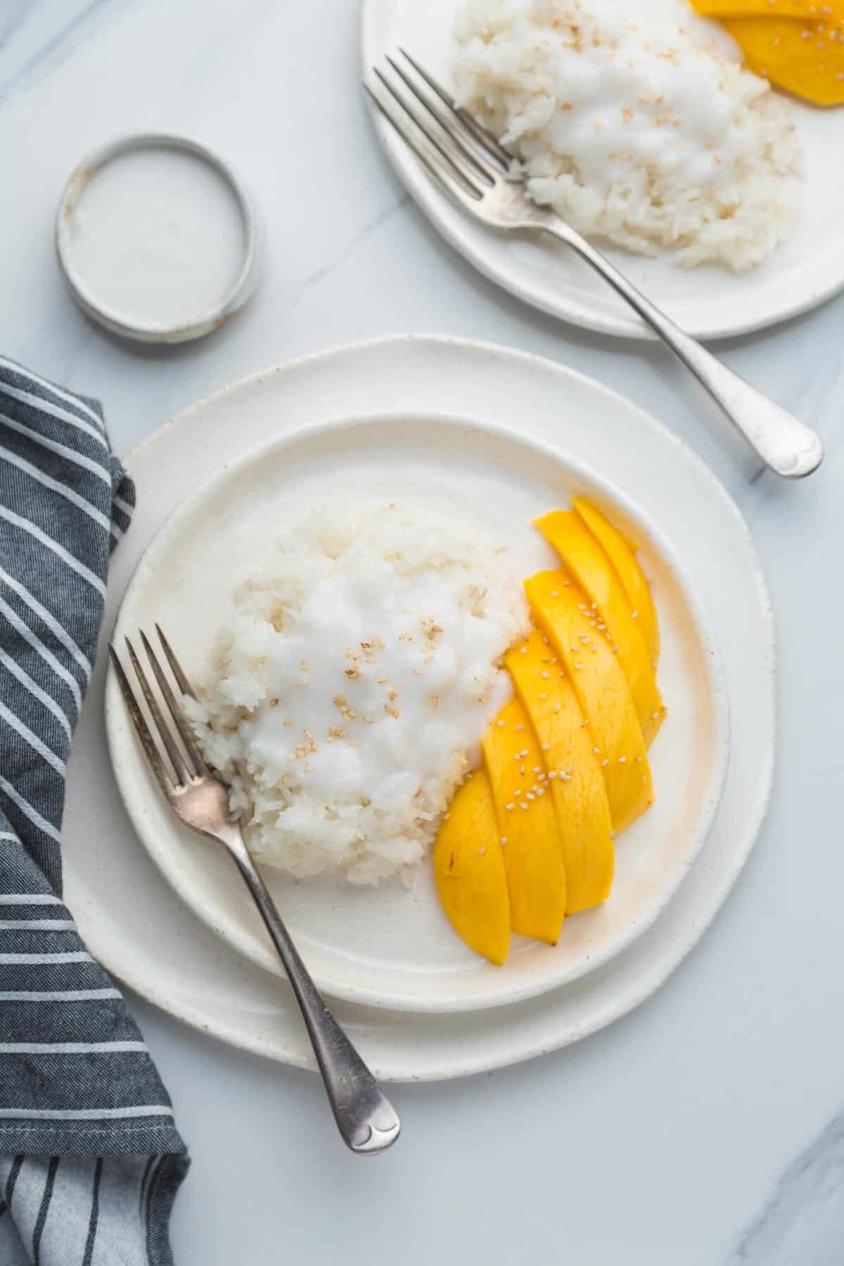 2 white plates with mango sticky rice, and 2 forks