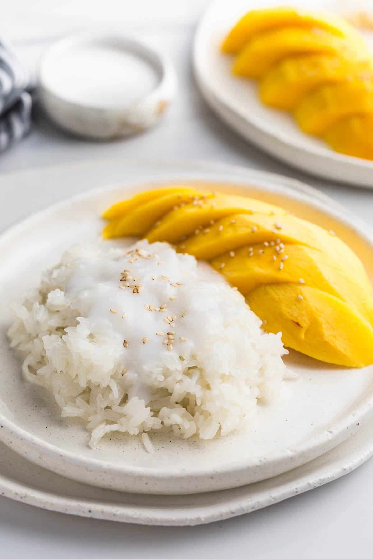 Mango sticky rice, with fresh mango on the side on a white plate. On a white ceramic tray