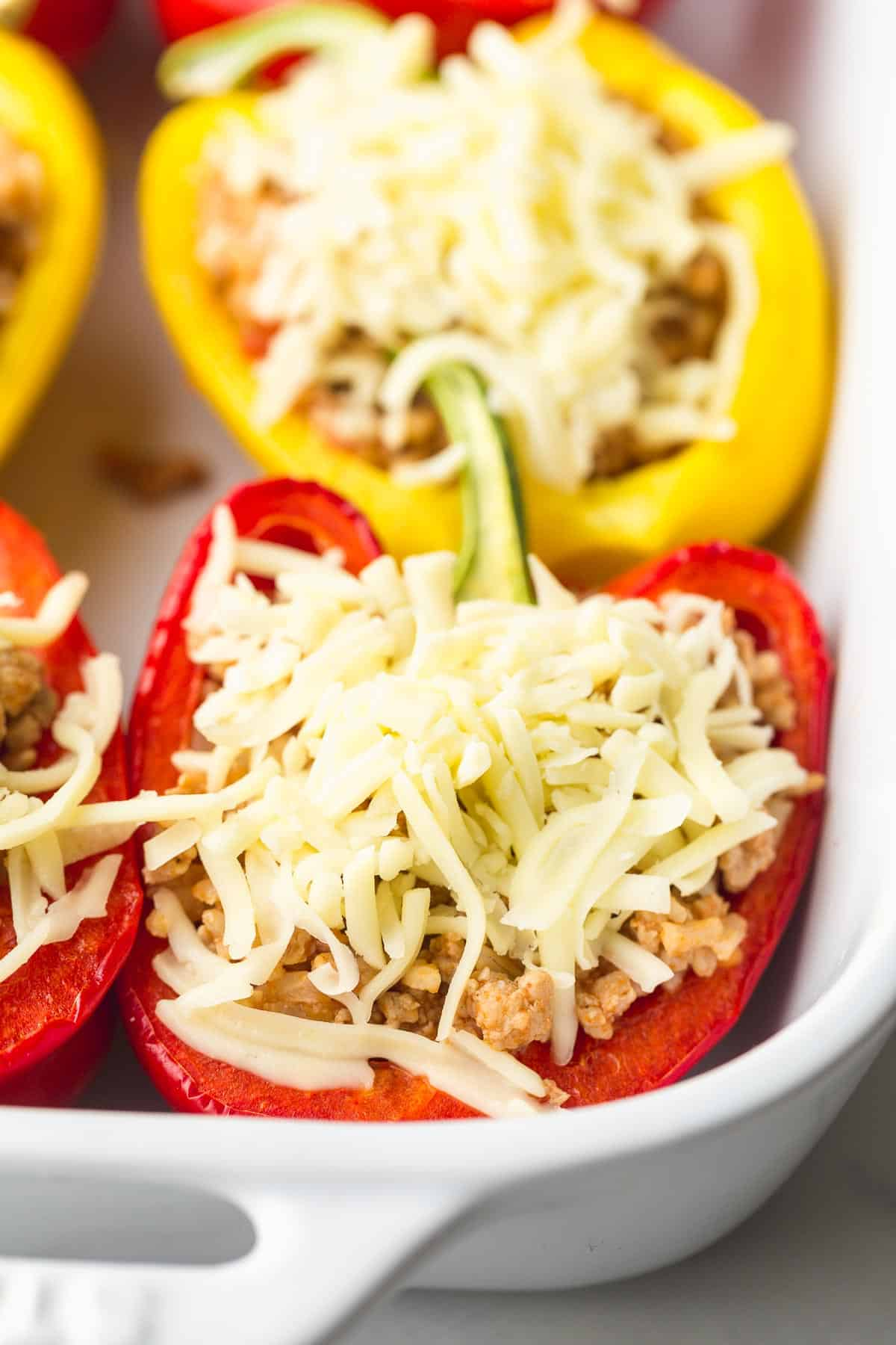 Topping the mexican stuffed peppers with cheese