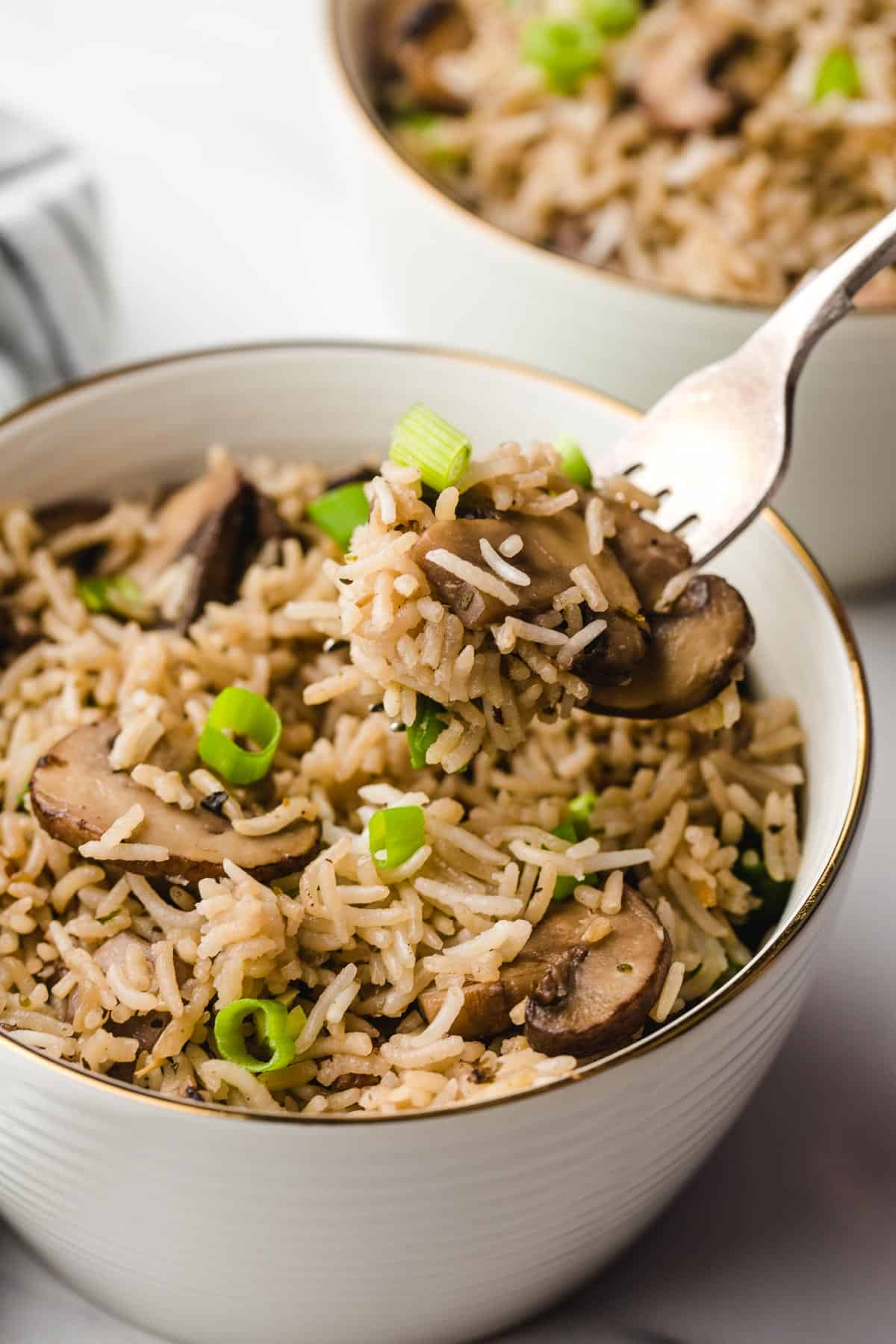 Eating mushroom rice with a fork from a bowl