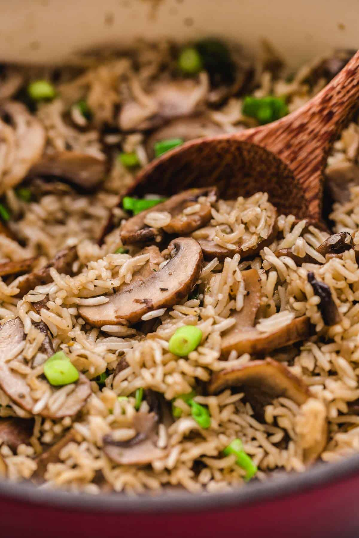 Mushroom rice in a pot with a wooden serving spoon