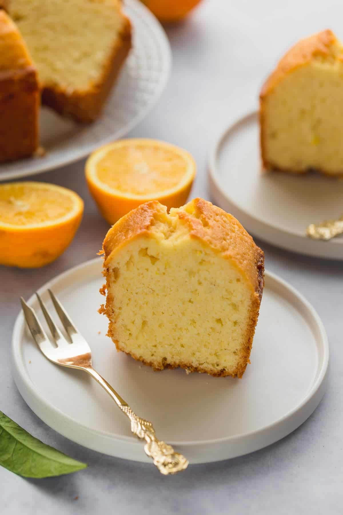 one slice of orange juice cake on a small cake plate with a golden fork