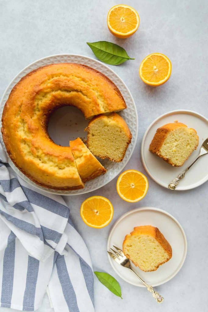 An overhead shot of orange juice cake, with 2 small plates and slices of cake with forks