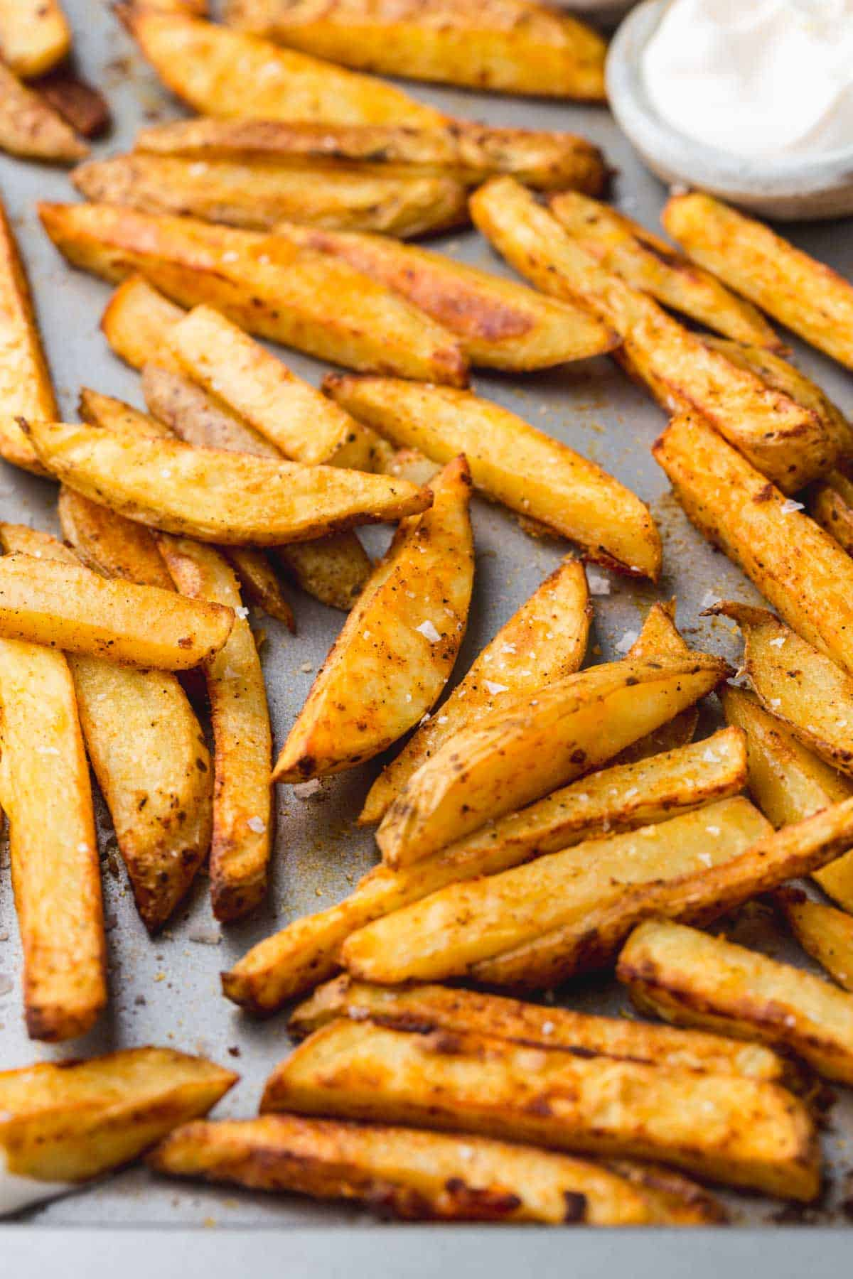 Oven baked fries on a baking pan, seasoned with sea salt flakes
