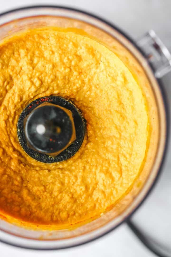 A close up of pumpkin hummus ready in a food processor