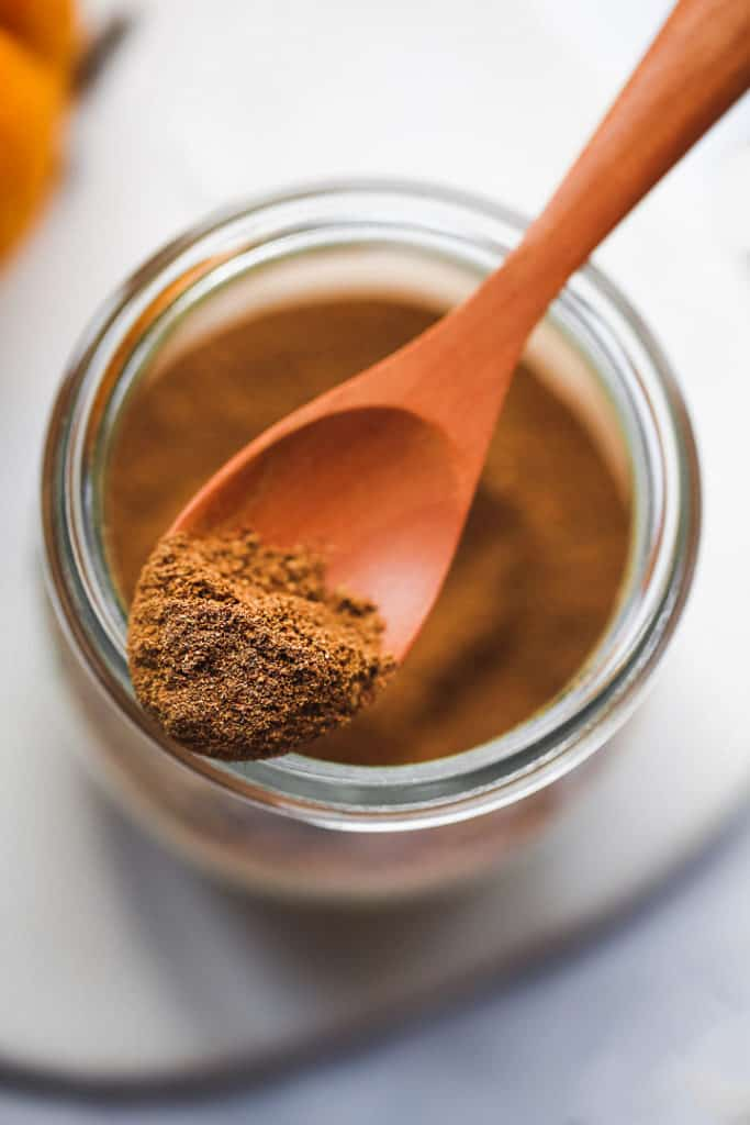 A close up shot of pumpkin pie spice on a wooden spoon