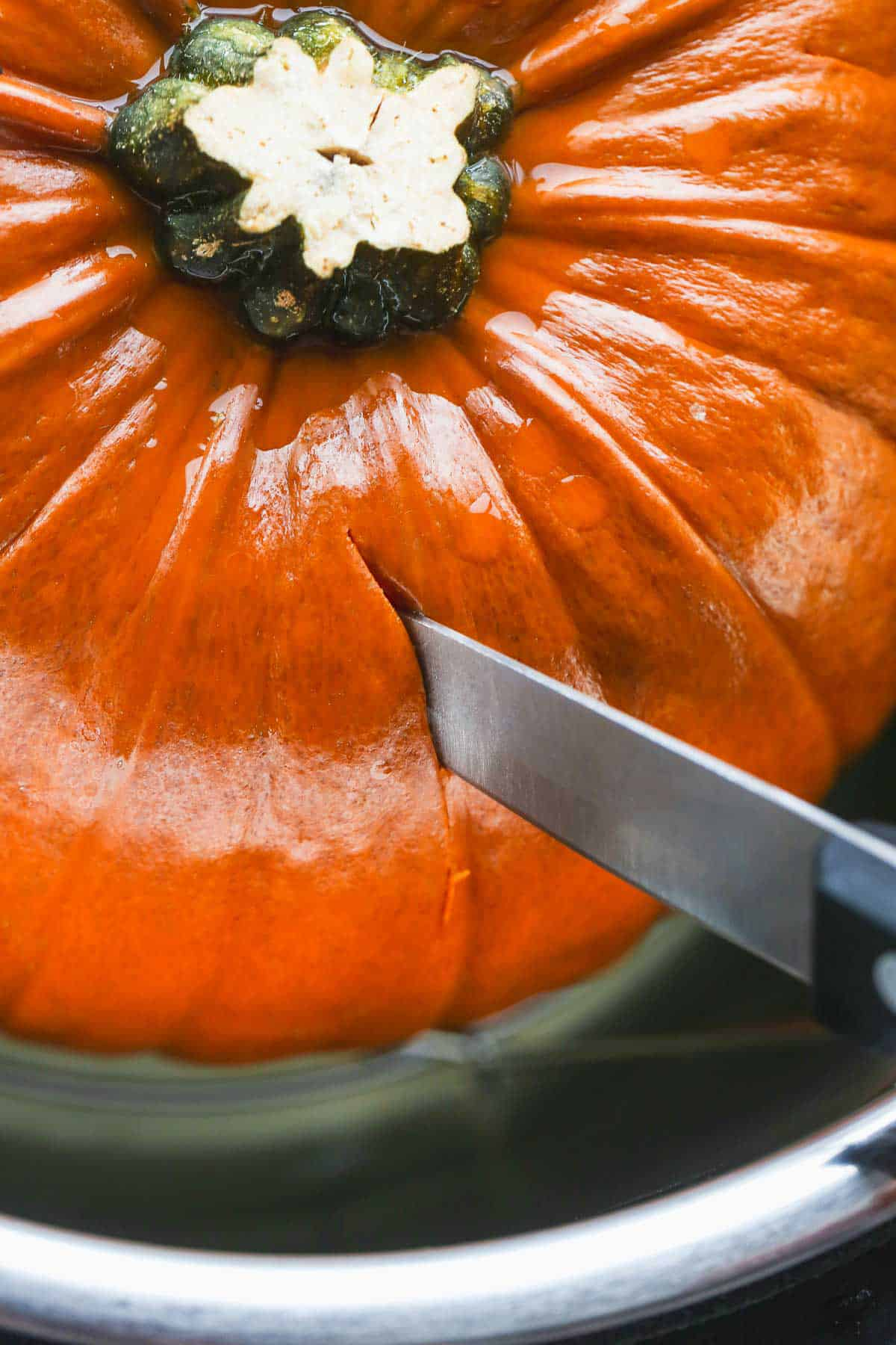 Cutting through the steamed pumpkin with a knife