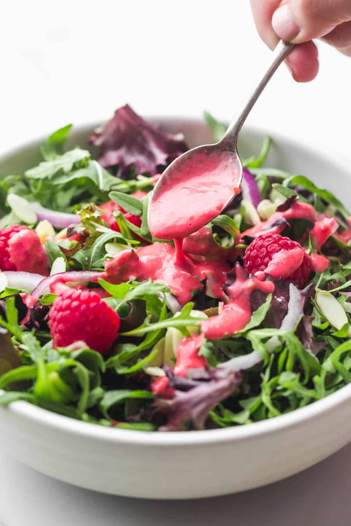 Drizzling Raspberry Vinaigrette over a mixed leaf salad with a metal teaspoon