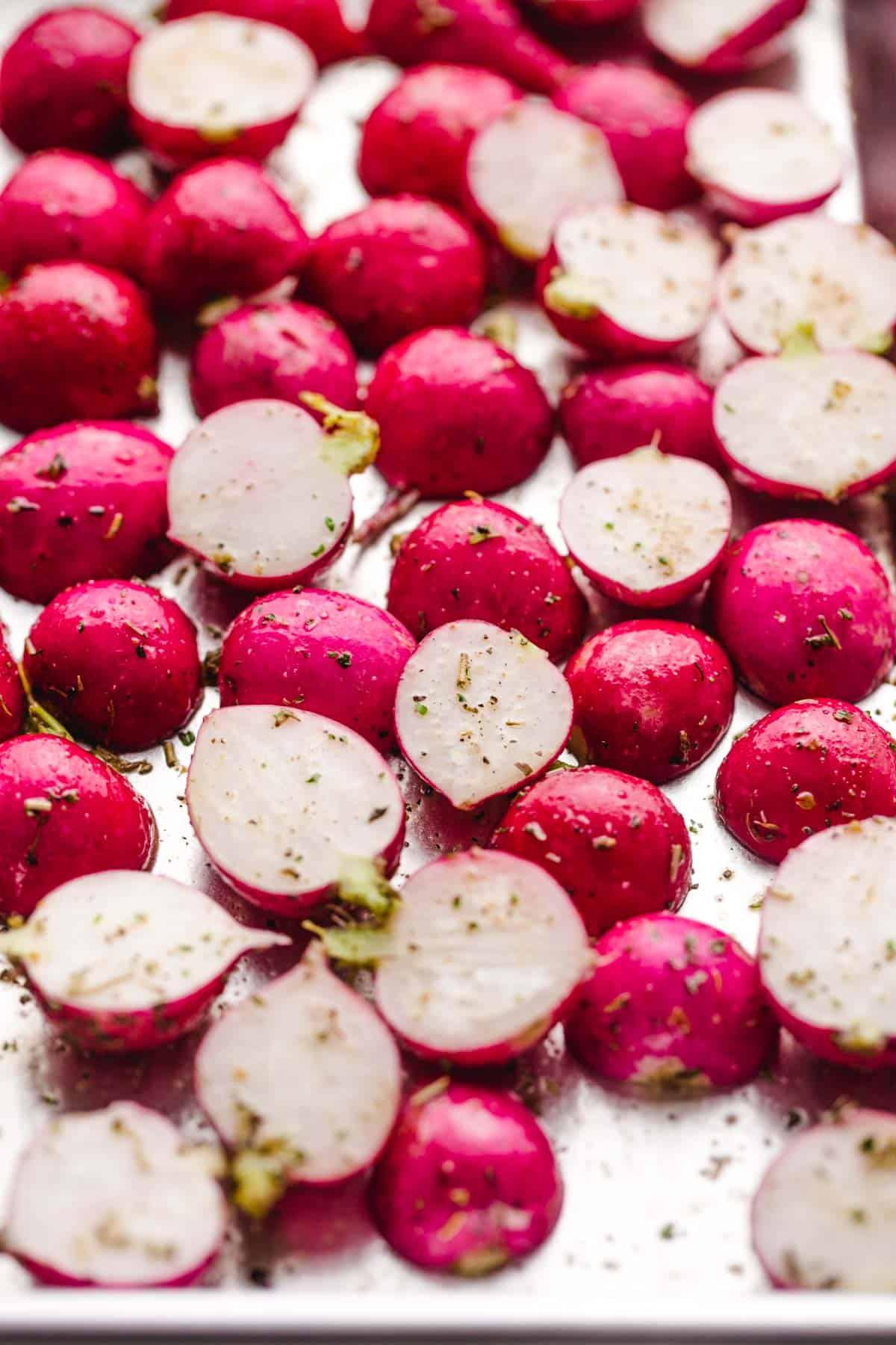 Seasoned radishes on a sheet pan before roasting