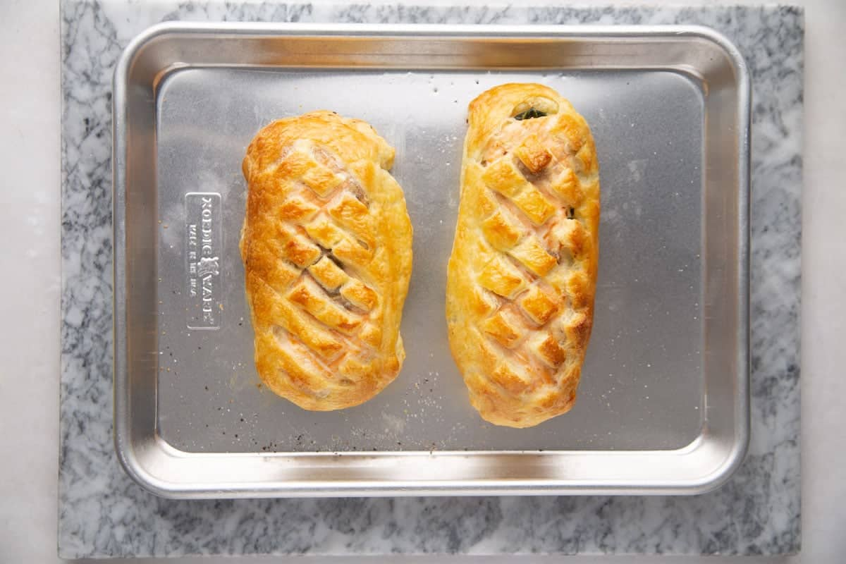 2 perfectly baked pieces of salmon wellington on a aluminium baking tray