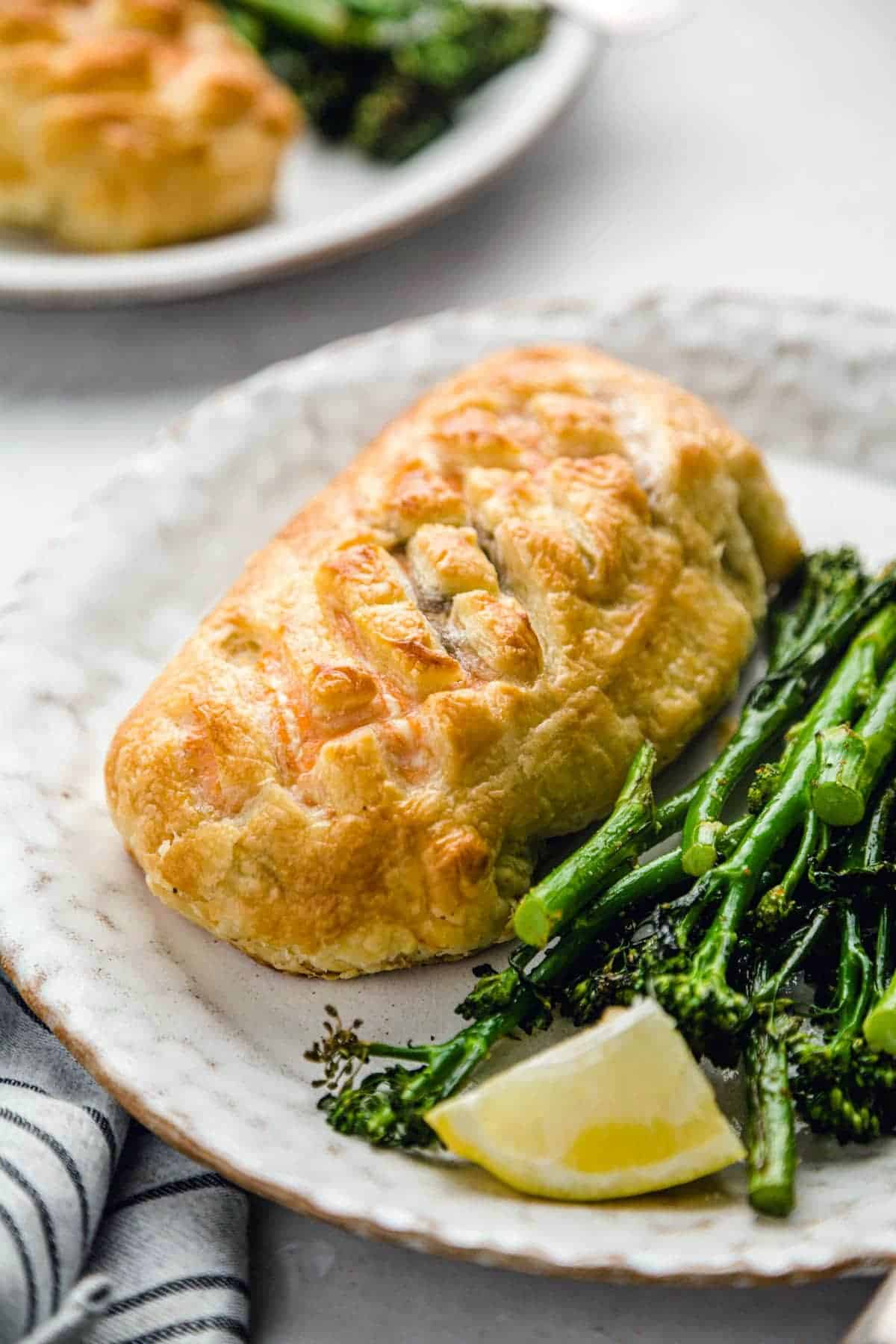 Salmon Wellington on a plate, served with steamed broccolini and a lemon wedge