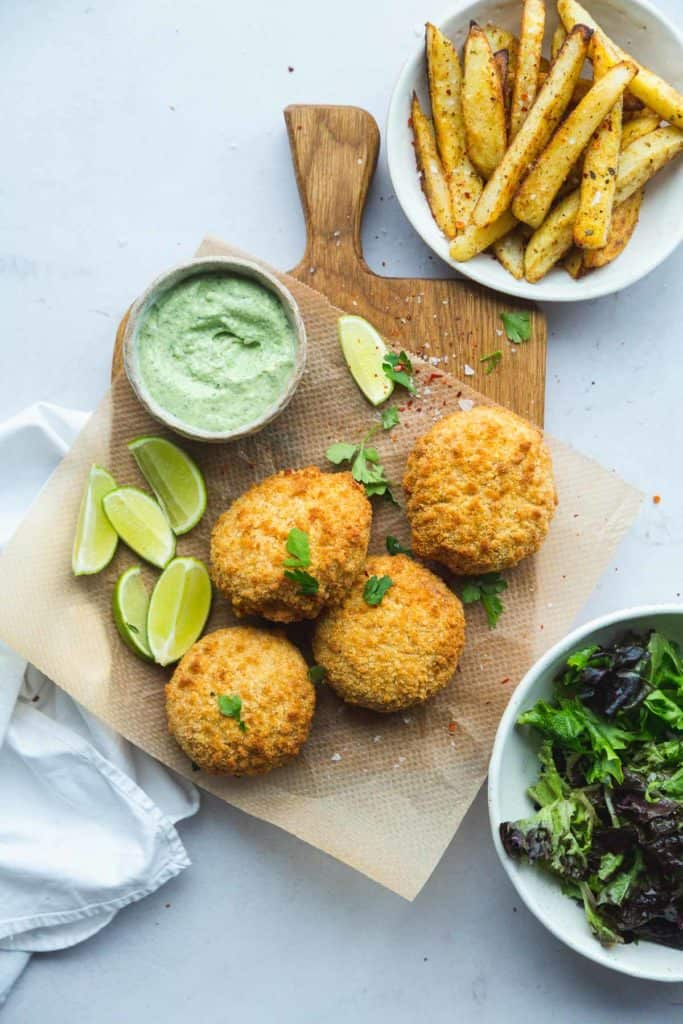 Fish cakes with chips, pesto mayo, slices of lime, and a side salad