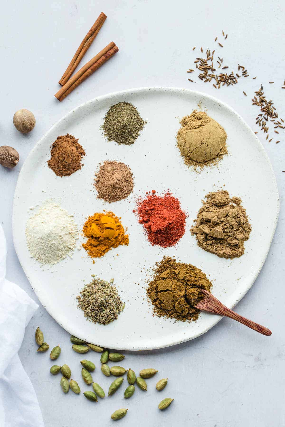 All the ground spices laid out of a round ceramic white tray, along with whole spices on the sides, and a small wooden spoon