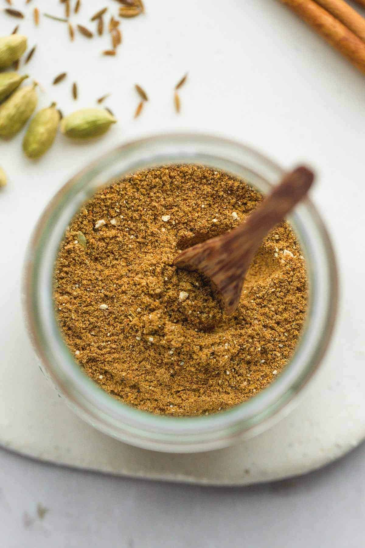 A jar of shawarma seasoning, top view, with a little wooden spoon
