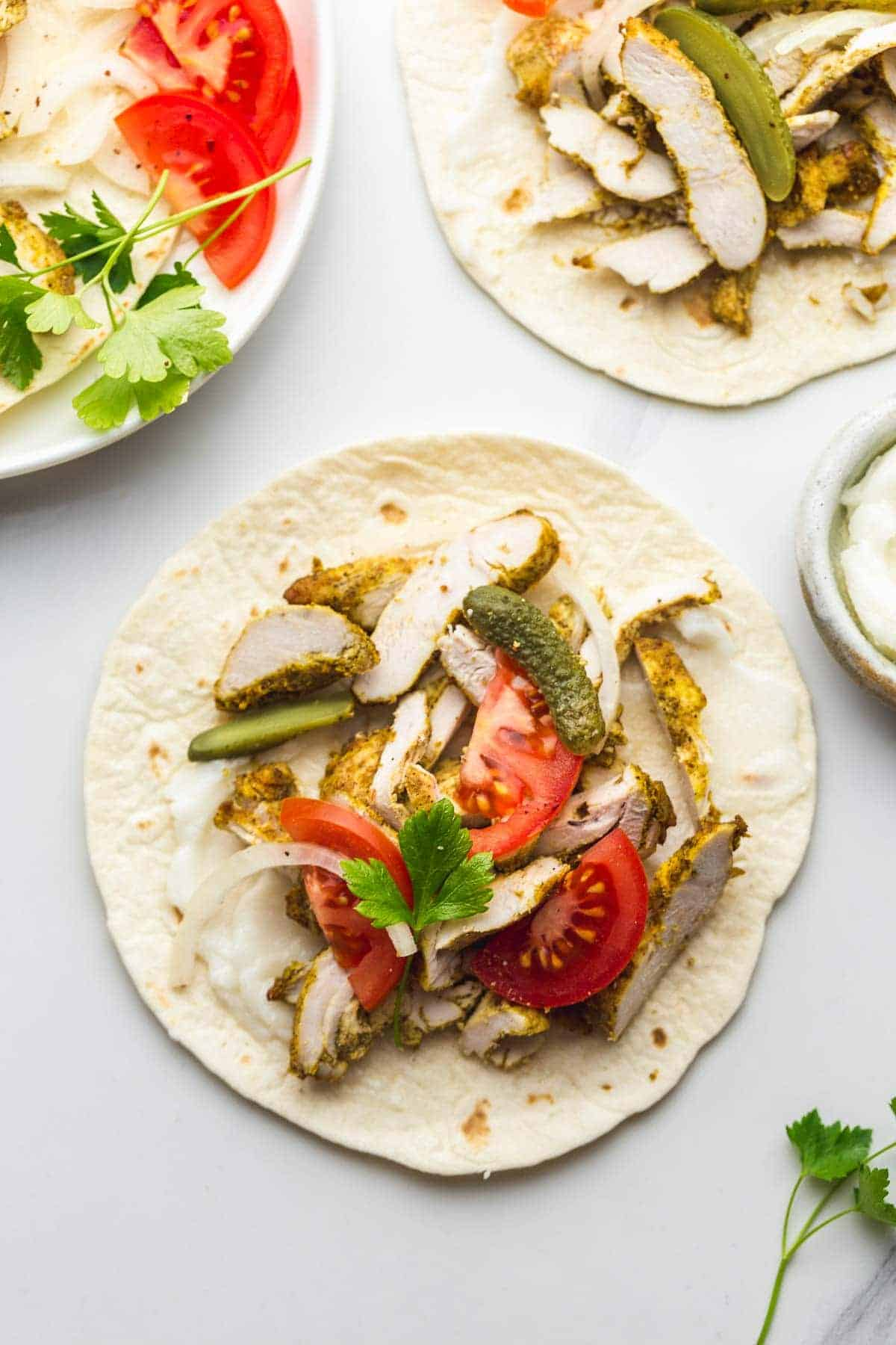 Chicken shawarma wraps or tacos with fresh tomato, pickles, and white onion slices