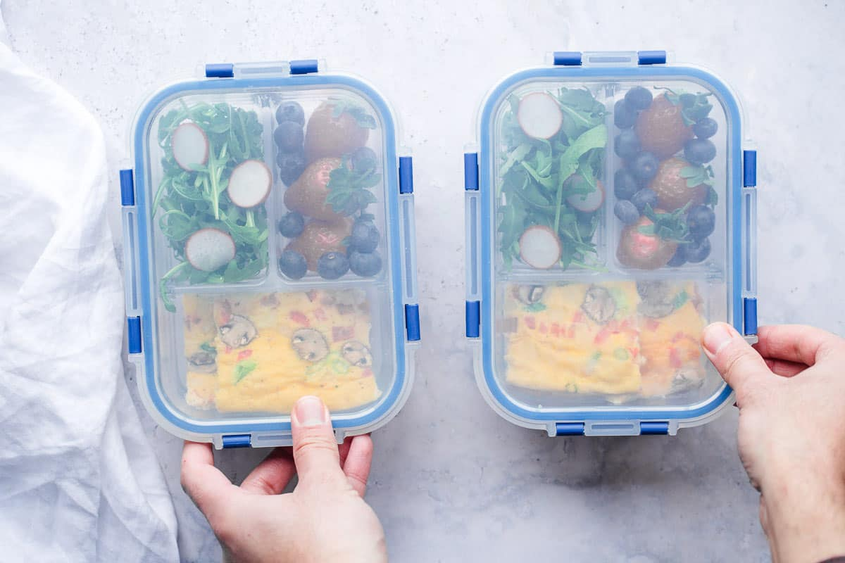 2 containers of meal prep with eggs, arugula, and berries