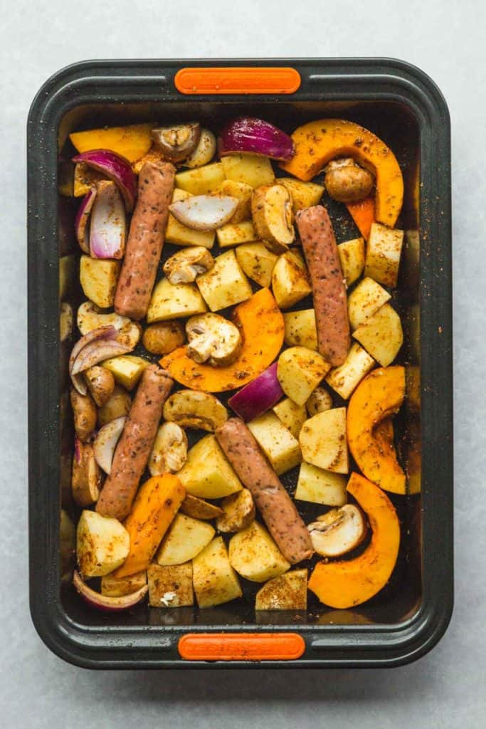 Chopped veggies and sausages in a roasting tin with seasonings and olive oil