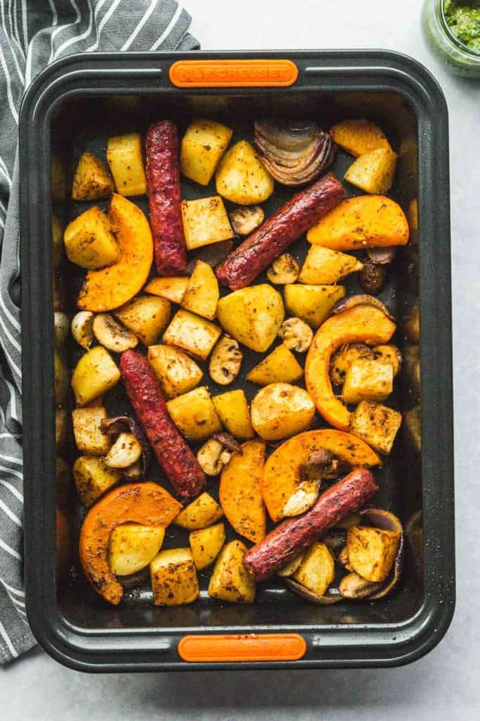 Roasted vegan sausages and potatoes, squash, mushrooms and onions in a roasting tin.