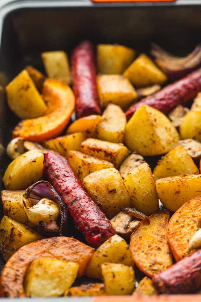 A close up shot of a cooked sausage and potatoes