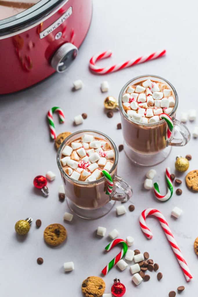 Slow cooker hot chocolate in 2 mugs, with a red crockpot at the back