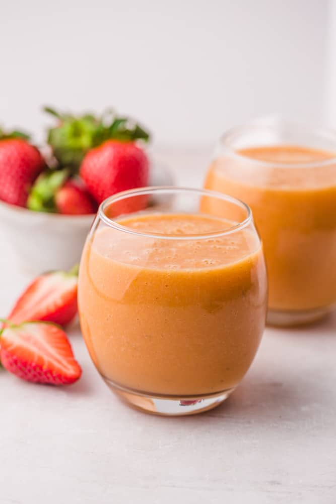 2 glasses of orange colored smoothie, and strawberries