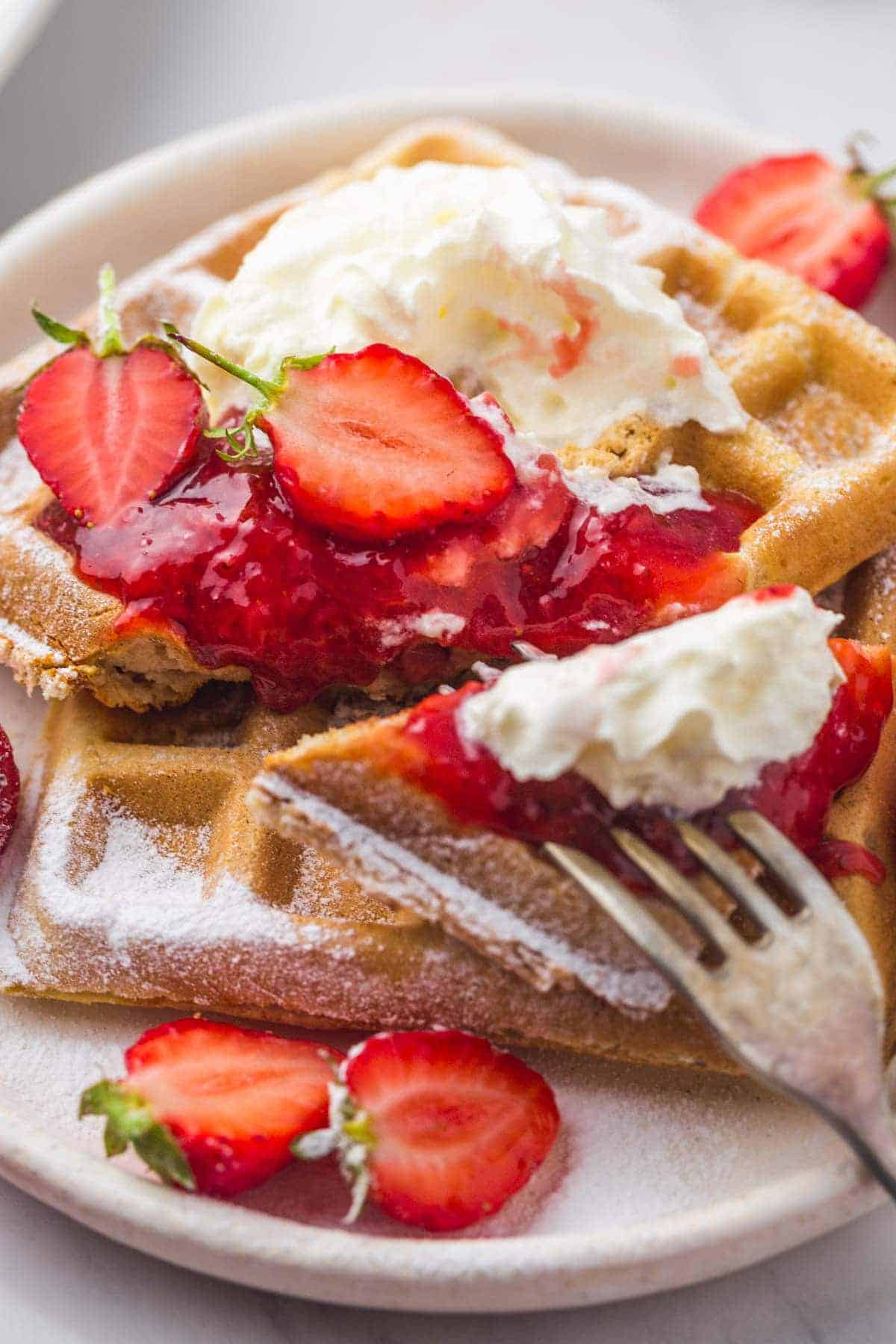 Strawberry sauce on strawberry waffles with cream