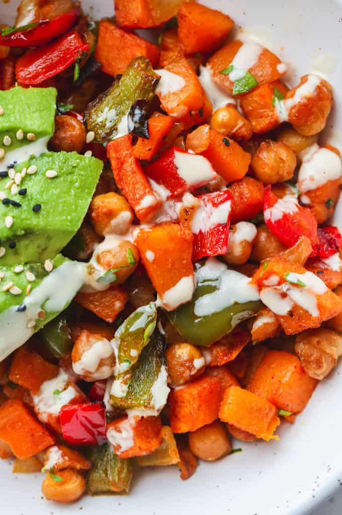 A close up shot of sweet potato hash with a drizzle of tahini dressing