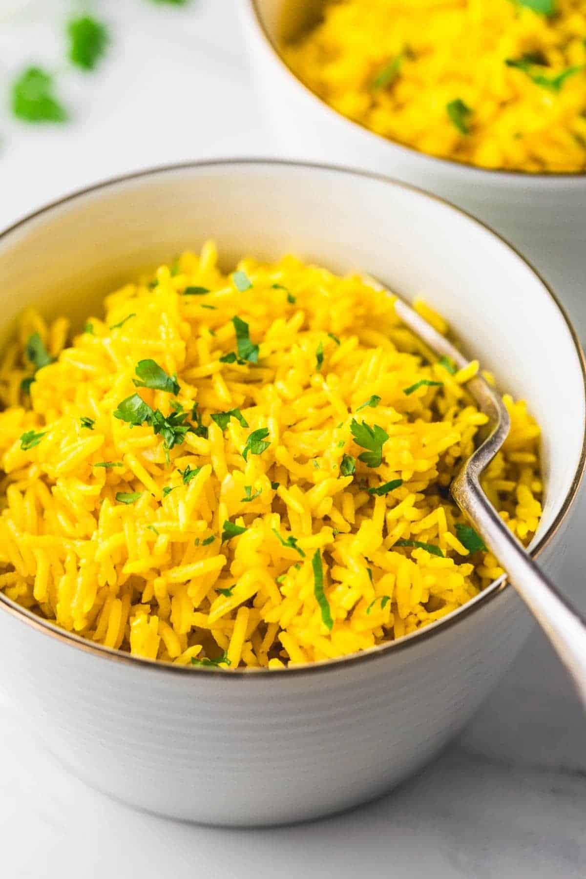 Yellow rice served in a white bowl with a fork on the side