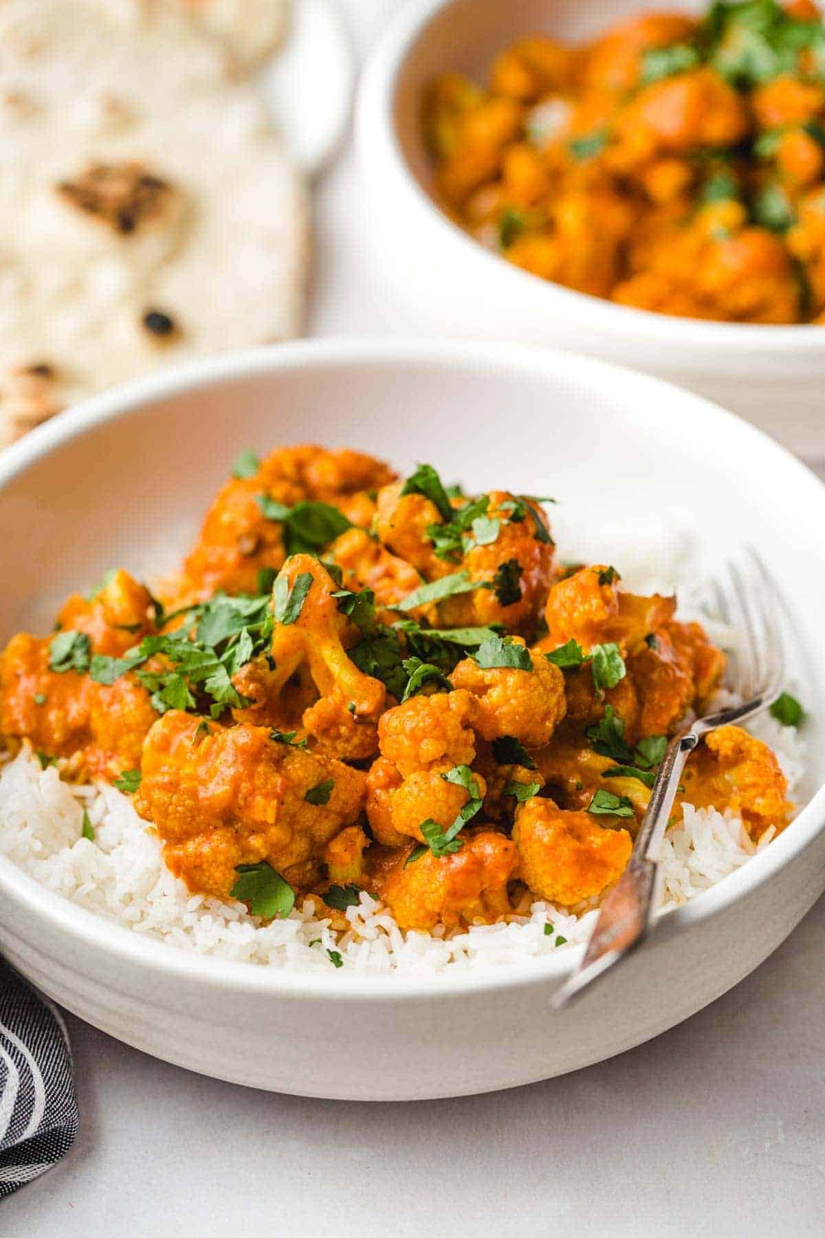 Serving butter cauliflower over basmati rice in white bowls