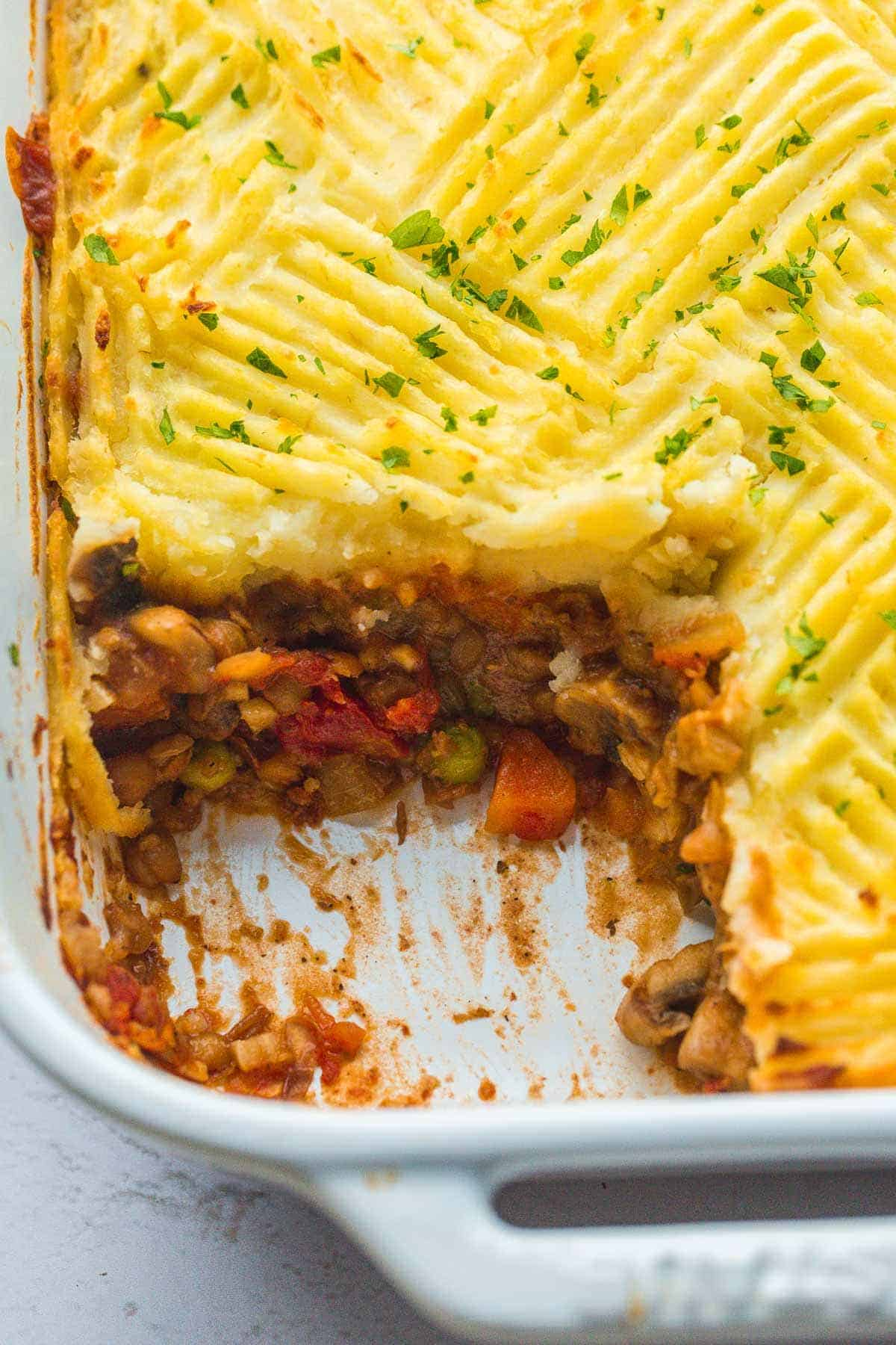 A close up picture of vegan shepherd's pie in a white baking dish