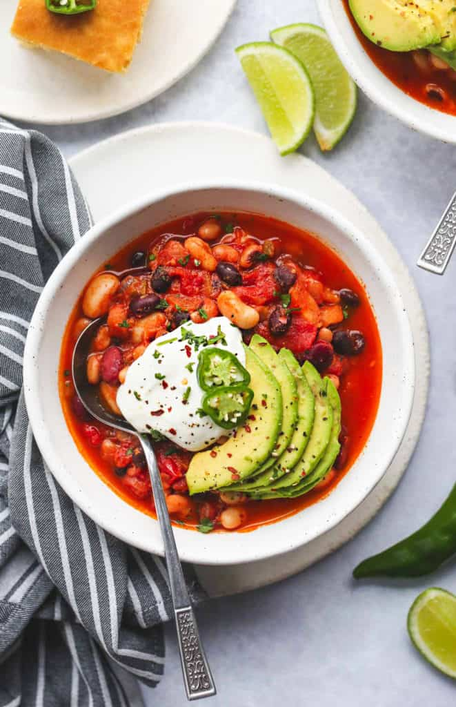 Vegan chili in a white bowl, topped with avocado, vegan sour cream, and jalapeño slices. Overhead shot.
